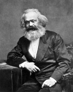 Abgebildet ist Karl Marx in einer sitzenden Position, der Kamera zugewandt.
